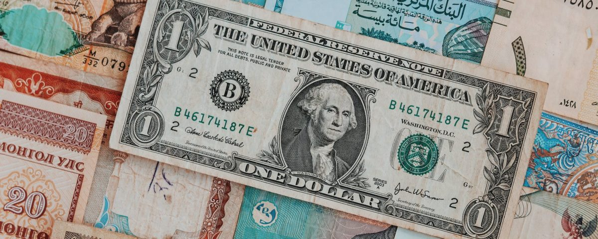 collection of banknotes with dollar bill on top